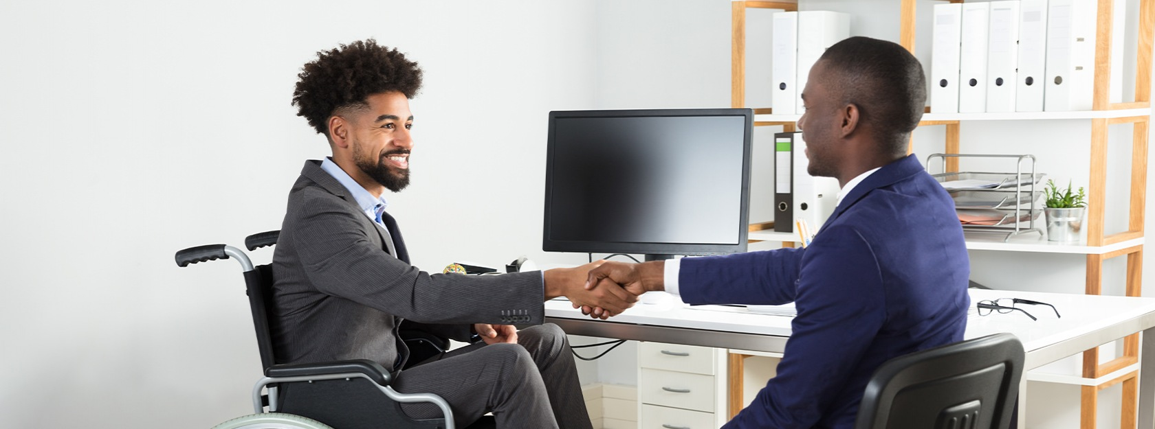 Men shaking hands in front of a desktop computer